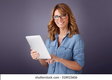 Portrait of middle age woman holding in her hand a digital tablet while looking at camera and smiling.