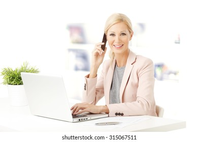 Portrait of middle age woman sitting at office and working. Beautiful businesswoman sitting at desk in front of laptop and making call.