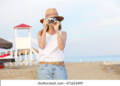 Portrait of a middle age woman wearing straw hat and standing on the beach while taking a photo with her vintage camera.