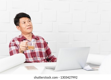 Portrait of Middle aged Asian handsome architect, in checked shirt, taking a short break, Absent-minded, contemplating at office with helmet, tablet, coffee and documents in background