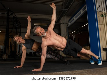 Portrait of a middle aged attractive couple who is doing a weight training together and having fun. The athletic man and woman are doing t pushups.