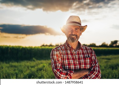 portrait of middle aged bearded man with hat, standing arms crossed and looking at camera, outdoors in meadow