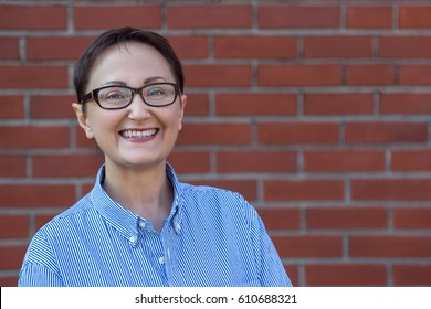 Portrait of middle aged business woman wearing glasses and shirt on a blurred brick wall background with a copy space on the right.