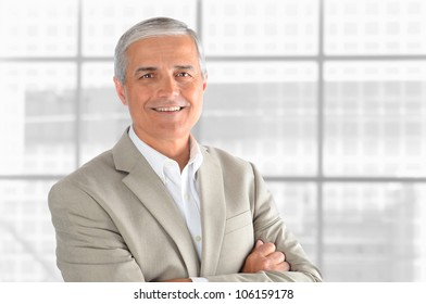 Portrait of a middle aged businessman in front of office window. Man is smiling and has his arms folded. Horizontal format.