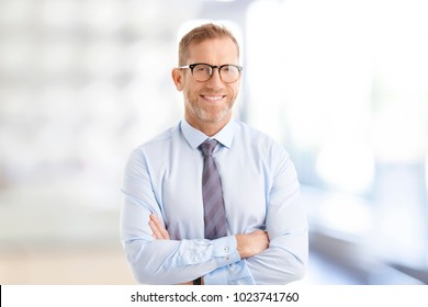 Portrait of middle aged businessman wearing shirt and tie while standing with arms crossed at the office.