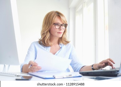 Portrait of middle aged businesswoman doing some paperwork and typing on laptop while sitting at office desk and working online.