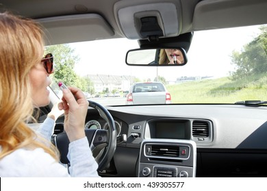 Portrait of middle aged businesswoman driving car and applying her makeup.