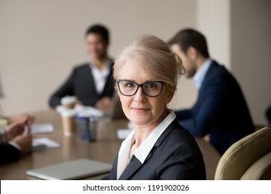 Portrait of middle aged businesswoman shooting making professional picture during office meeting with colleagues, confident female employee posing looking at camera at business briefing in boardroom