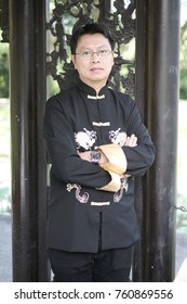 Portrait of middle aged of Chinese business man Chinese black outfit at the park in summer
