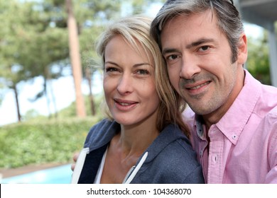 Portrait of middle aged couple sitting outside the house
