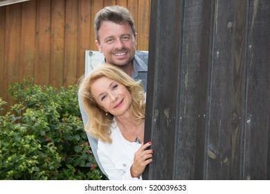 Portrait of middle aged couple standing outside the house
