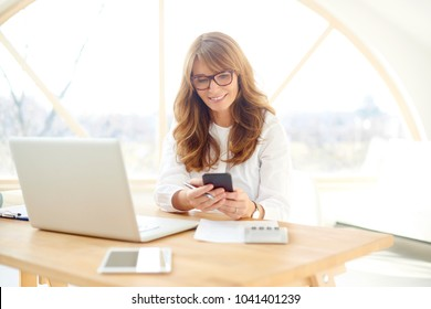 Portrait of middle aged entrepreneur businesswoman using mobile phone and text messaging while sitting at desk in front of laptop. Home office.