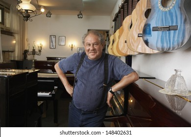 Portrait of middle aged male owner leaning in music store