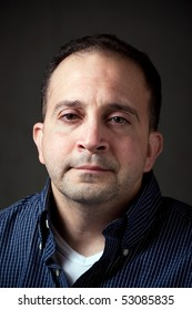 Portrait of a middle aged man in his upper thirties with a serious or concerned expression on his face.