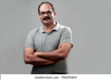 Portrait of a middle aged man of Indian origin with folded hands