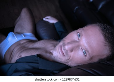 Portrait of a middle aged man sitting in leather armchair in his underwear and sixpack abs looking at camera