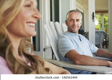 Portrait of middle aged man sitting on chair with woman in foreground at porch