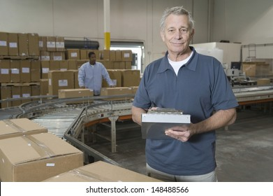 Portrait of a middle aged man with worker in background at distribution warehouse