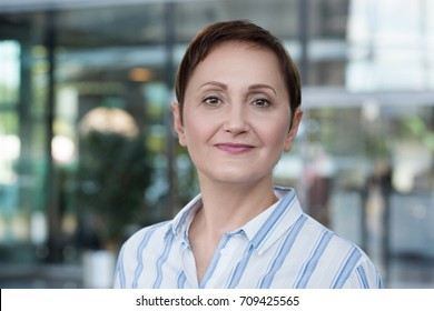 Portrait of a middle aged older business woman looking at the camera and smiling. Head shot of a businesswoman in the office or business centre.