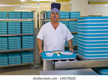 Portrait of middle aged porter with plastic trays in hospital kitchen