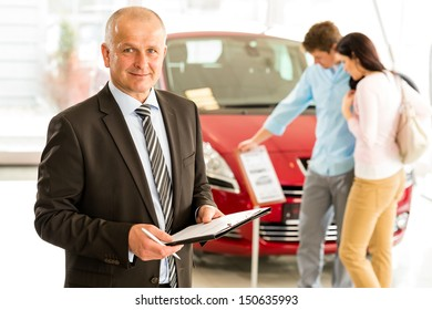 Portrait of middle aged salesman in car retail store