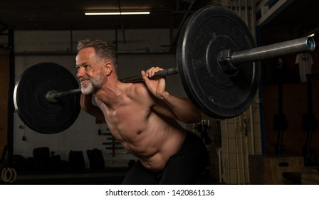 Portrait of a middle aged strong athlete who is doing weight training in a gym. The athletic man in his fifties is shirtless and doing the exercise clean and jerk with barbells.