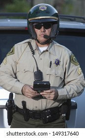 Portrait of middle aged traffic cop with clipboard standing against car
