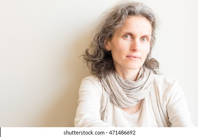 Portrait of middle aged woman with grey hair and cream clothing