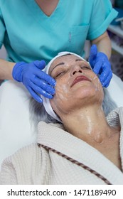 Portrait of middle aged woman having face treatment at beauty clinic