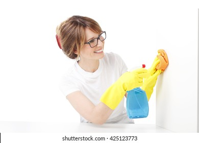 Portrait of middle aged woman holding a spray bottle and sponges in her hand while doing housekeeping. Isolated on white background.