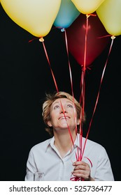 Portrait of middle aged woman holding colorful balloons and looking up isolated on black background.