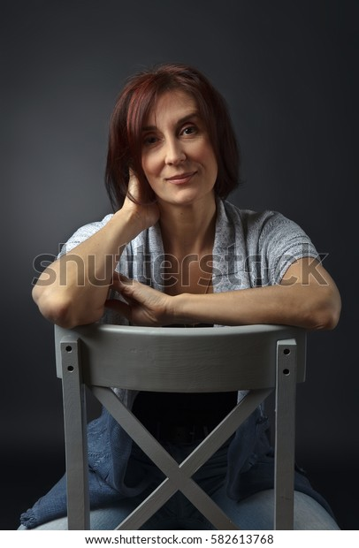 portrait of middle aged woman on a gray chair, studio shot