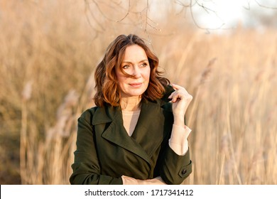 portrait of middle aged woman posing at the park