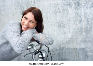 Portrait of a middle aged woman smiling and leaning on bicycle
