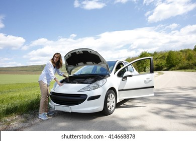 Portrait of middle aged woman standing next to her broken down car on the road and checking engine oil.