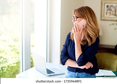 Portrait of middle aged woman using mobile phone and making a call while working from home. Home office.