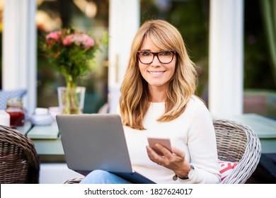 Porträt von Frauen mittleren Alters mit Laptop und Textnachrichten während der Arbeit zu Hause im Garten. Heimbüro.