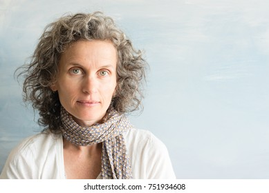 Portrait of middle aged woman with wavy grey hair and scarf against blue background (selective focus)