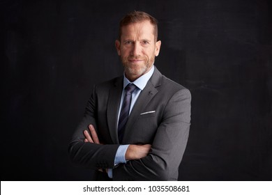 Portrait of middle aged wrinkled businessman with arms crossed wearing suit while posing at dark background.