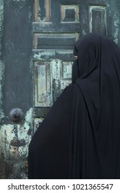 Portrait of a Middle Eastern woman wearing a black Niqab Impossible to recognize this woman behind this complete attire