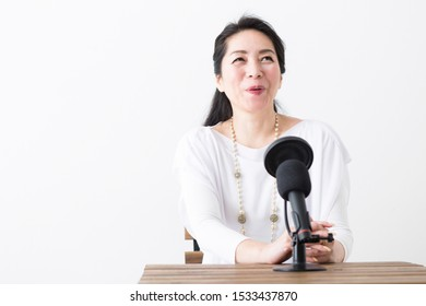 Portrait of middle woman in front of white wall