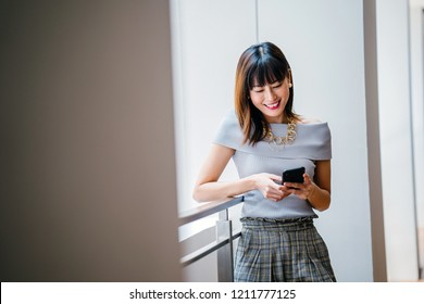 Portrait of a middle-aged Asian woman in a grey outfit learning on a ledge during the day. She is messaging on her smartphone and smiling brightly as she uses her device.