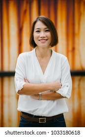 Portrait of a middle-aged and attractive Chinese Asian woman against a creative, artistic background of a rust-stained wall. She is in smart casual (white shirt, jeans) and is smiling. Arms crossed.