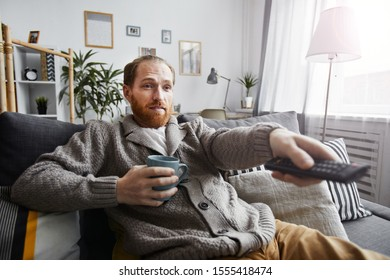 Portrait of middle-aged bearded man watching TV at home and switching channels via remote control while relaxing on comfortable couch