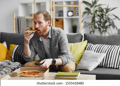 Portrait of middle-aged bearded man watching TV at home and eating pizza during lazy weekend, copy space