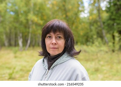 portrait of a middle-aged brunette woman on a background of nature
