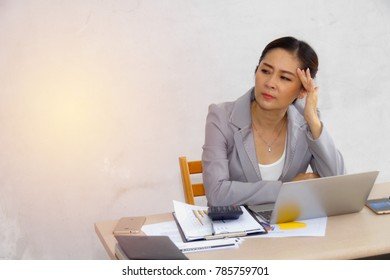 Portrait of middle-aged business woman using thoughts sitting on the desk with anxiety.