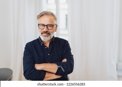 Portrait of middle-aged cheerful man wearing glasses standing with arms crossed