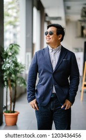Portrait of a middle-aged Chinese Asian man (Singaporean) in smart casual standing in the city. He is well-dressed and groomed in a navy suit, oxford button-down shirt and jeans with sunglasses.
