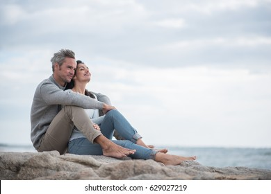 Portrait of a middle-aged couple sitting on a rock at the beach. They are wearing sweaters and jean, the man has grey hair